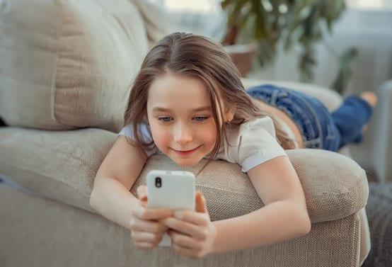 Mädchen mit Smartphone auf der Couch