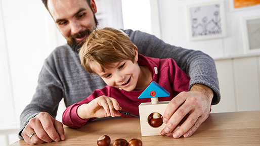 Kastanienbasteln macht Spaß: Vater bastelt mit Sohn