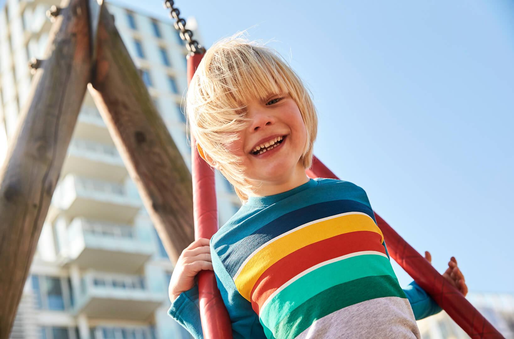 Junge spielt draußen auf der Schaukel