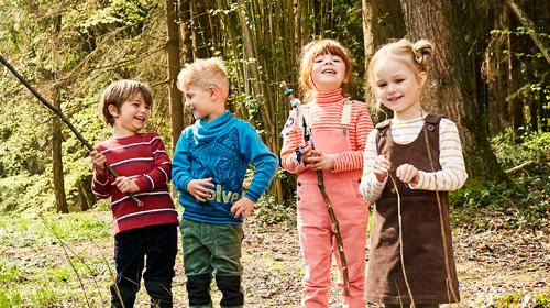 Kinder mit Stöcken im Wald
