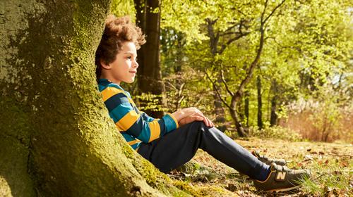 Junge sitzt an einem Baum im Wald