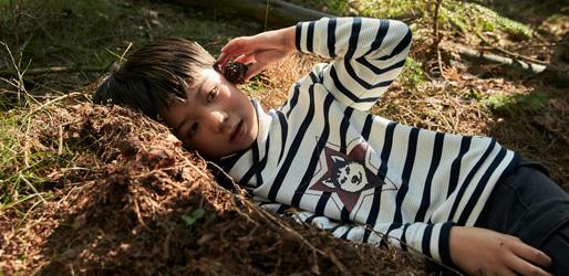 Kind liegt auf der Walderde