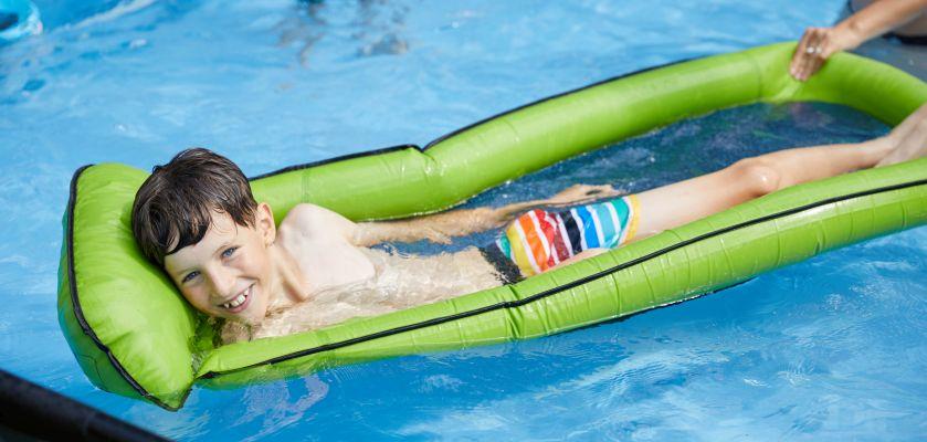 Kinder im Wasser: Junge mit Luftmatratze