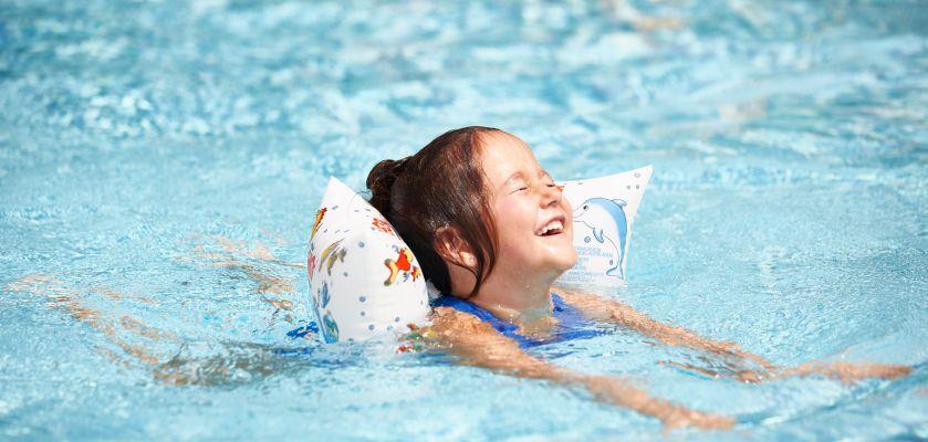 Kinder im Wasser: Mädchen mit Schwimmflügeln
