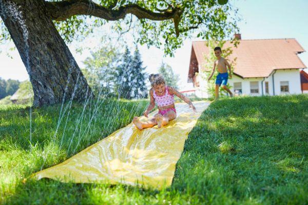 Kinder im Wasser: Wasserrutsche im Garten