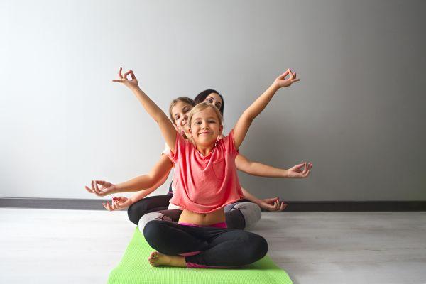 Sport mit Kindern: Familie macht Übungen auf Turnmatte