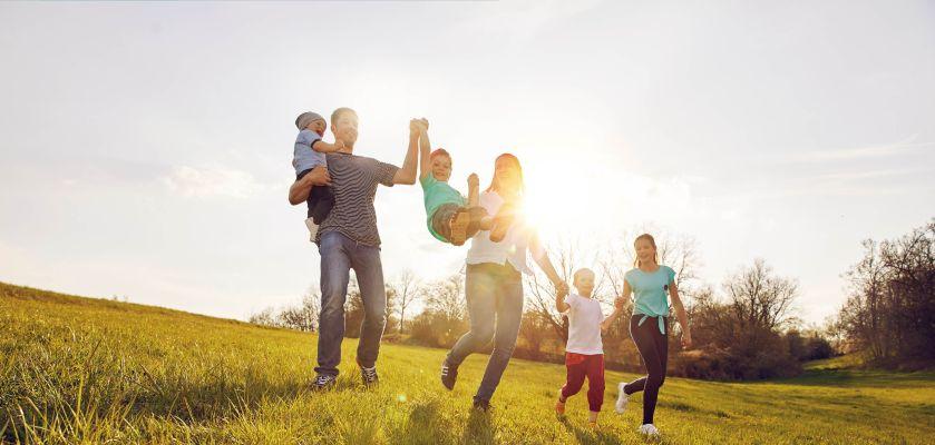 Familie macht auf der Wiese Sport mit Kindern