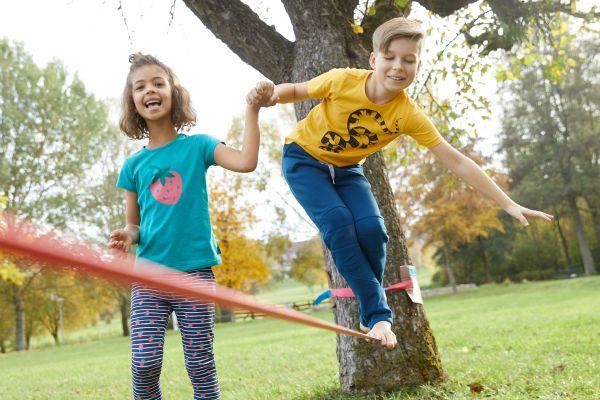 Sport im Park: Kinder spielen mit Slackline