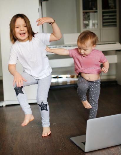 Sportübungen für Kinder: Geschwister beim Tanzen