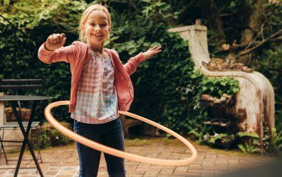 Sportübungen für Kinder: Mädchen mit Hula-Hoop