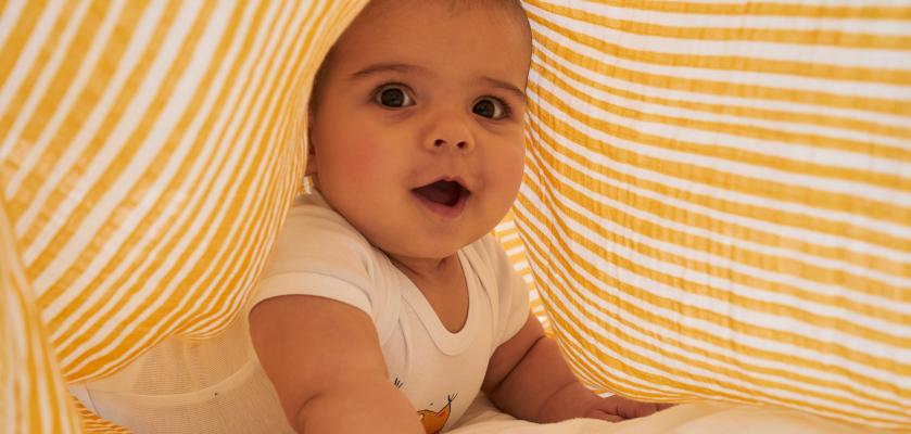 Babys im Sommer anziehen: Baby unter luftigem Musselin-Tuch