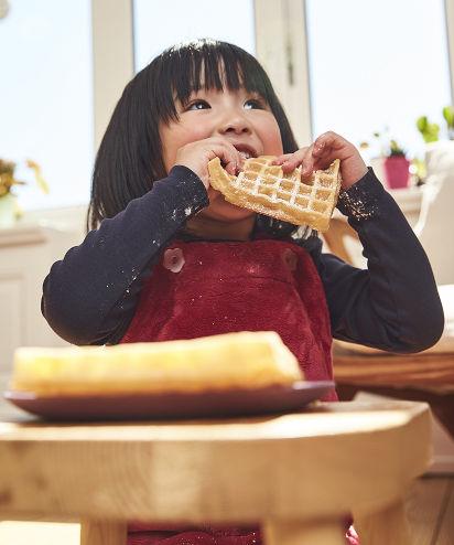 Backen für den Kindergeburtstag: Mädchen isst leckere Waffeln