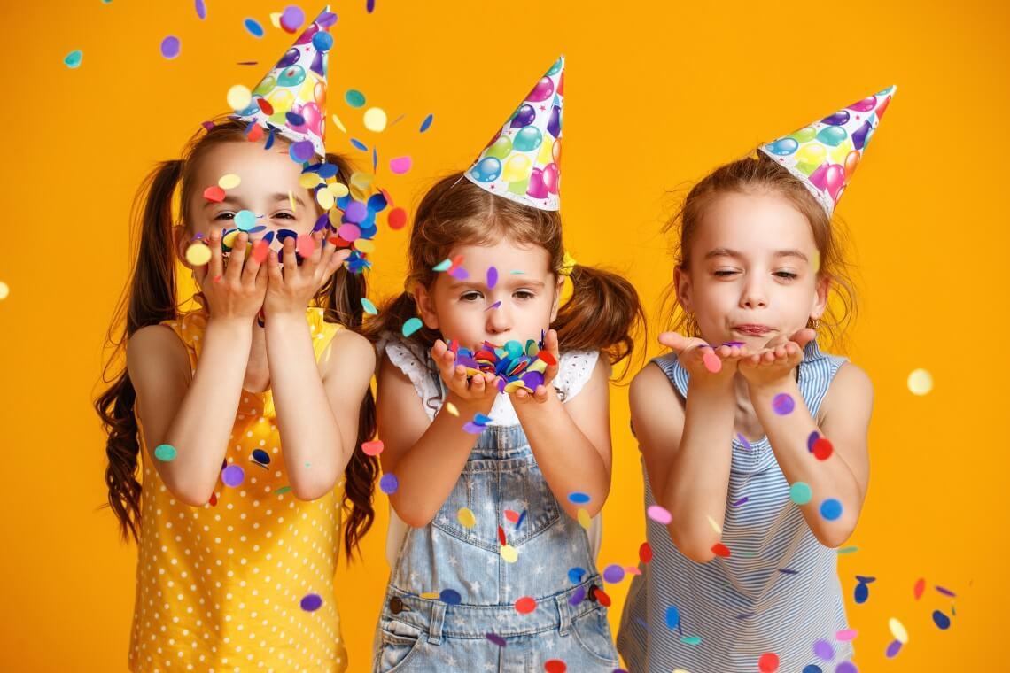 Backen mit Kindern: Kinder mit Partyhütchen und Konfetti