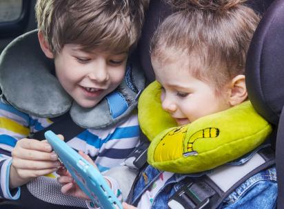 Spiele im Auto: Geschwister spielen im Auto mit einem Tablet