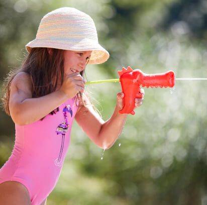 Wasserspiele mit Kindern: Kind mit Wasserspritzpistole