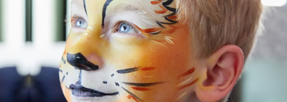 Kinderschminken zu Fasching: Junge mit geschminktem Löwen-Gesicht