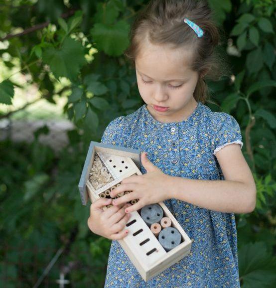 Mädchen pflegt selbst gebautes Insektenhotel