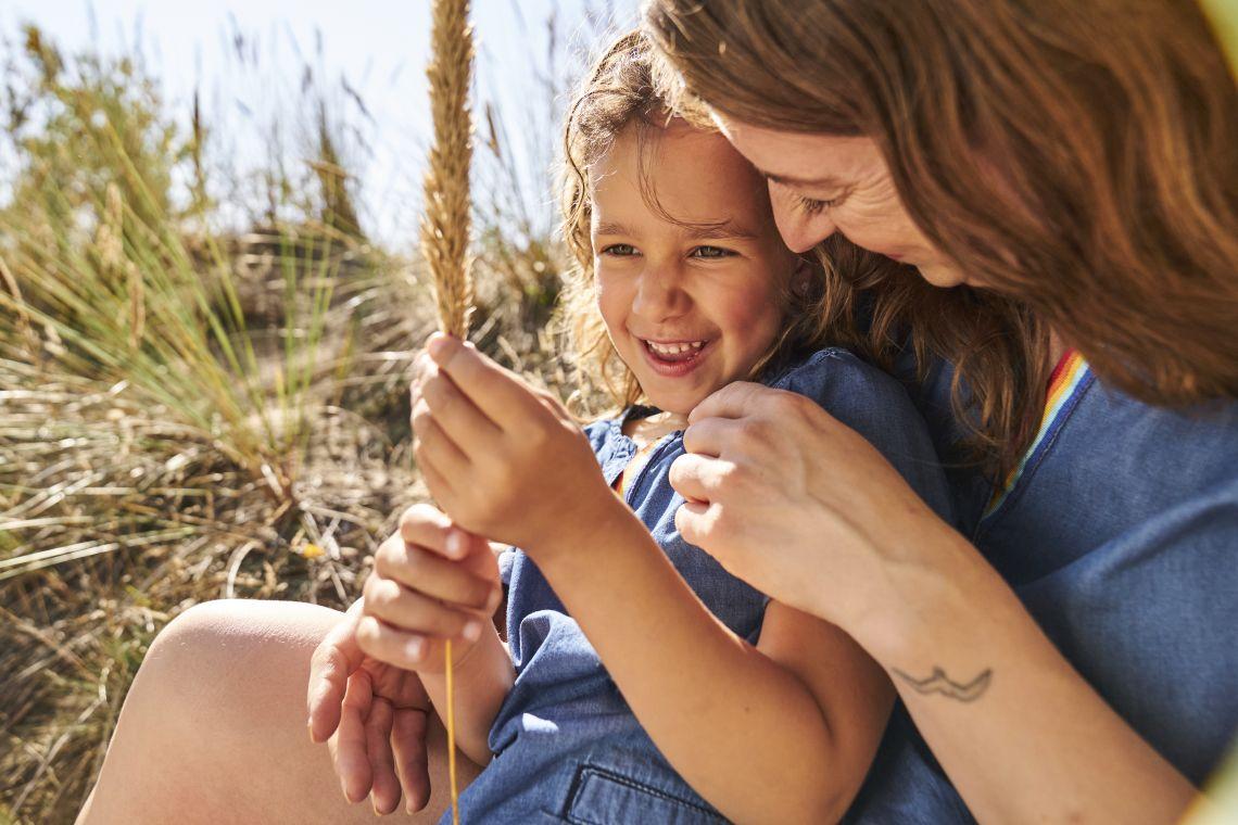 Familienzusammenhalt: Mutter sitzt mit Kind im Gras