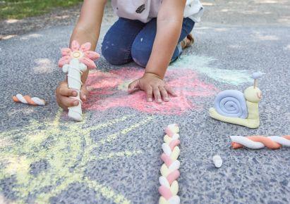 Gartenspiele: Mädchen malt mit Straßenmalkreide