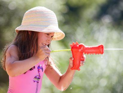 Mädchen spielt Gartenspiel mit Wasserpistole