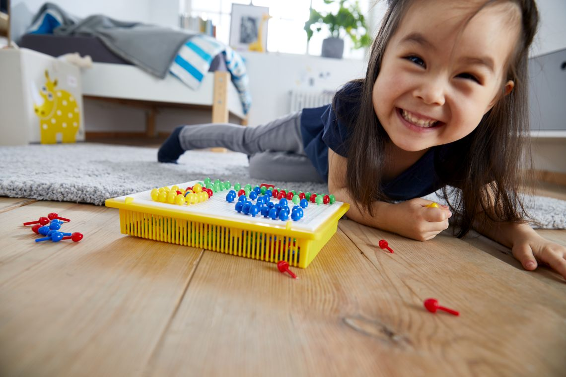 Basteln mit Kindern: Mädchen spielt Steckspiel