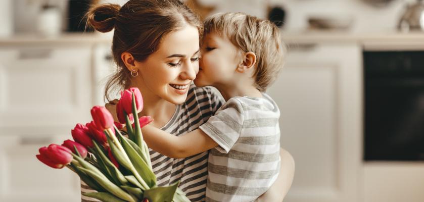 Muttertagsgeschenke basteln: Kind umarmt Mutter und schenkt Blumen