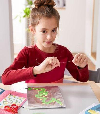 Spiele selber machen: Mädchen bastelt Spiel
