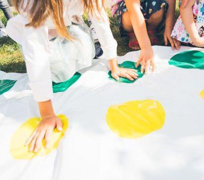 Spiele selber machen: Kinder spielen Twister im Park
