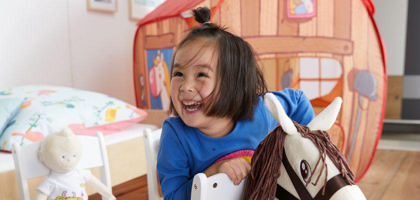 Spielen mit Kindern: Mädchen spielt im Kinderzimmer