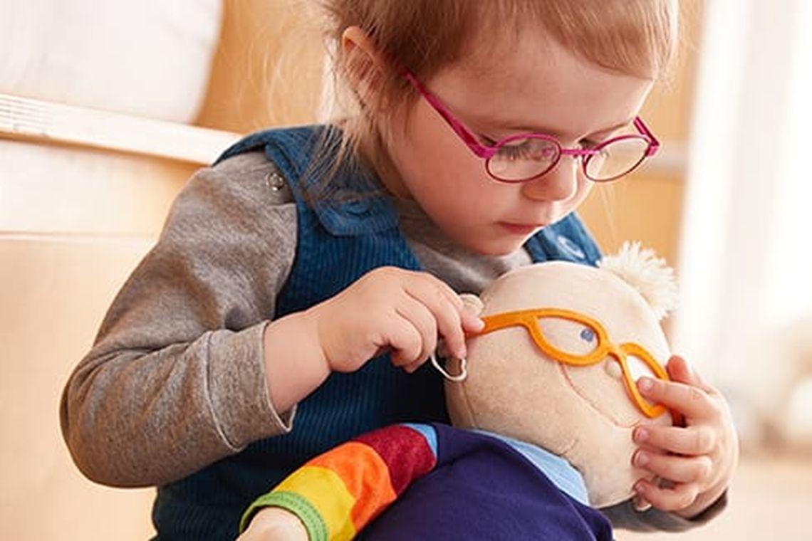 Spielen mit Kindern: Mädchen spielt mit Puppe