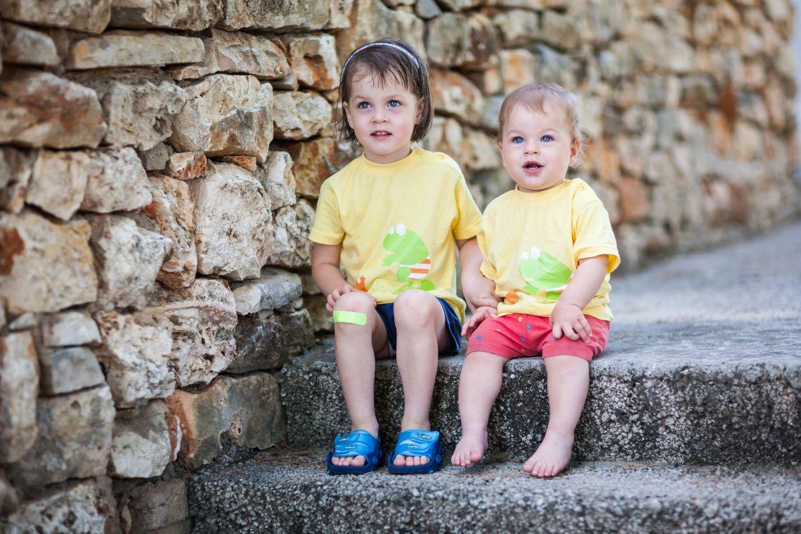 Ausflüge mit Kleinkind: Mädchen mit Pflaster am Knie sitzt mit Geschwisterchen auf einer Treppe