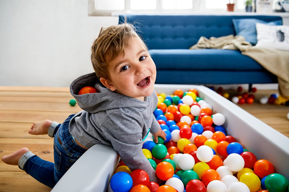 Alternative zu Ausflügen mit Kleinkind: Junge spielt im Bällebad