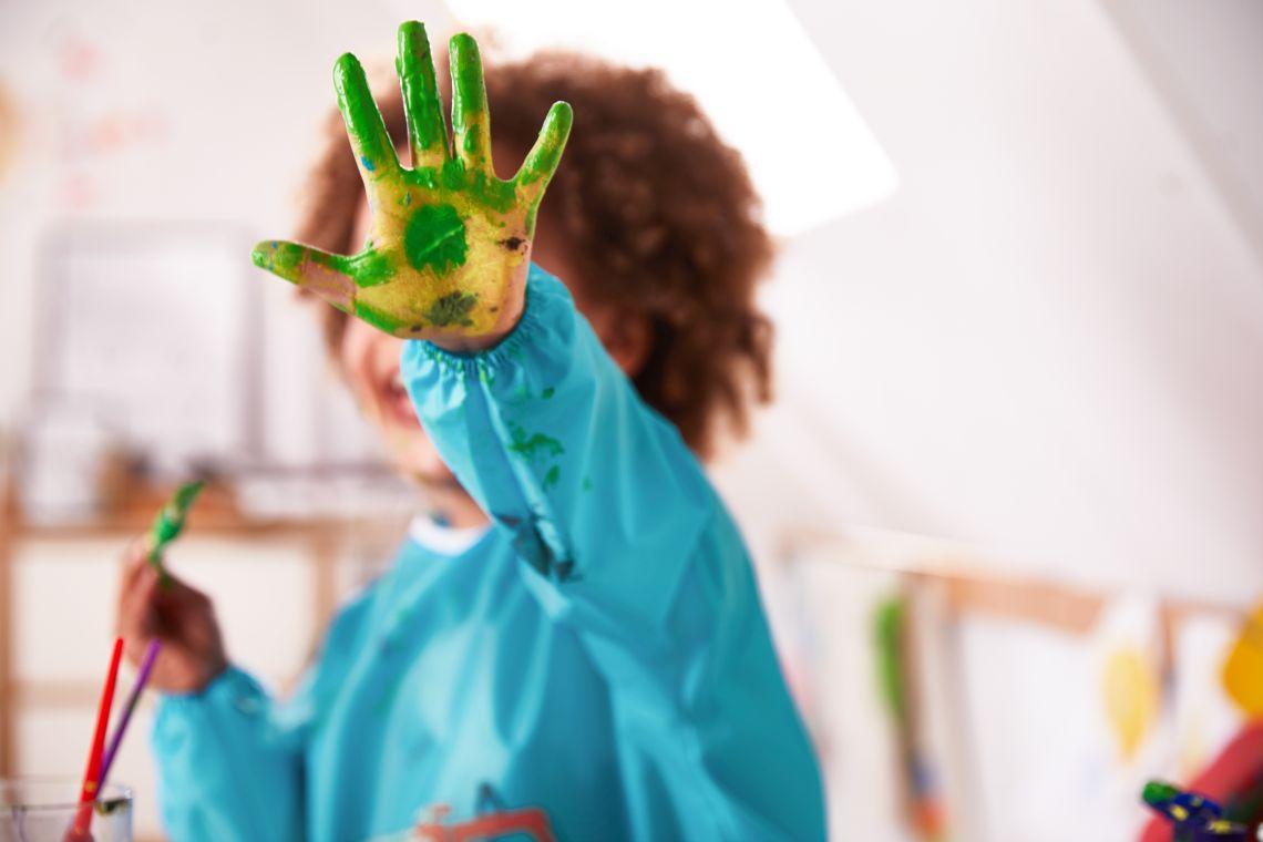 Alternative zu Ausflügen mit Kleinkind: Mädchen malt mit Farbe