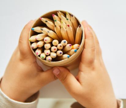 Vatertagsgeschenke basteln: Kinderhände halten Stiftebecher aus Papier