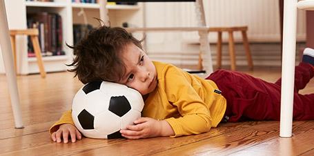 kleiner-junge-liegt-mit-fussball-auf-boden.jpg